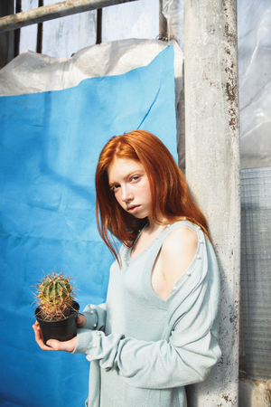 Portrait of a beautiful redheaded woman in dress holding a cactus in a glass house
