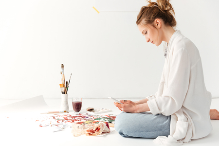 looking aside: Picture of serious young caucasian lady painter at workspace using mobile phone. Looking aside. Stock Photo