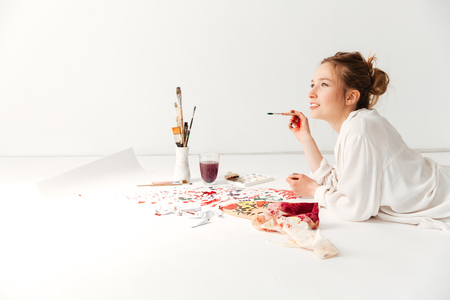 Image of concentrated young caucasian lady painter at workspace. Looking aside. Stockfoto