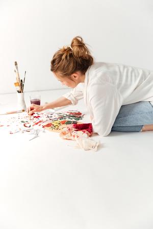 Afbeelding van geconcentreerde jonge Kaukasische dame schilder op werkruimte. Opzij kijken.