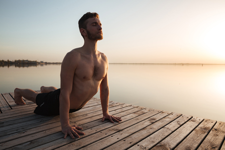 looking aside: Image of handsome young sportsman make yoga exercises at the beach.