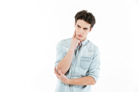 Portrait of a pensive young man looking away at copy space isolated over white background Stock Photo