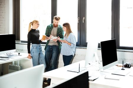 koncentrovaný: Obrázek mladých koncentrovaných kolegů v kanceláři mluví mezi sebou. Pohlédl stranou.