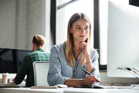 Foto van geconcentreerd jong vrouwenwerk in bureau die computer en grafische tablet gebruiken. Opzij kijken.