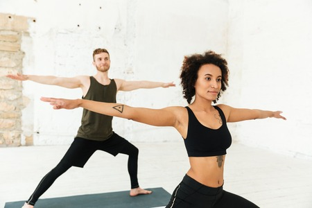 Youg african man and redhead man dressed tracksuits making exercises while doing yoga in gym