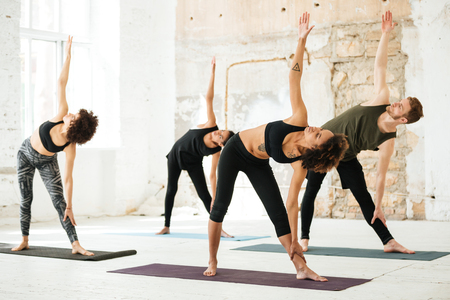 Horizontal image of young people doing yoga exercose in light gym Stock Photo