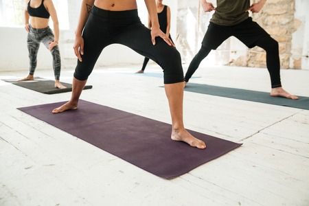 Cropped image of young healthy people doing yoga on mats Stock Photo