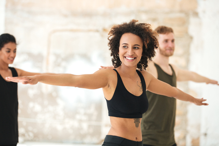 Smiling young african woman doing yoga exercises with group together indoors