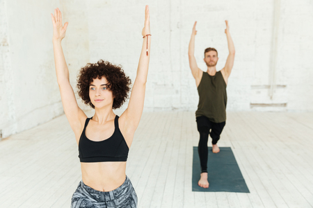 Young caucasian brunette pretty woman with curly hair raising her hands while making exercise in gym Stock Photo