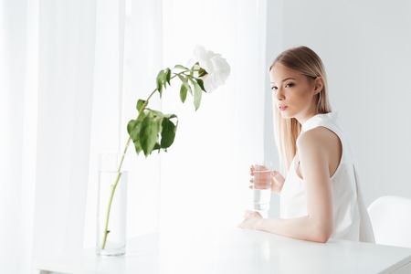 koncentrovaný: Picture of serious blonde lady sitting indoors near flowers dressed in white dress. Looking at camera. Reklamní fotografie
