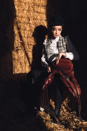 looking aside: Image of serious young girl sitting in barn with seddle. Looking aside