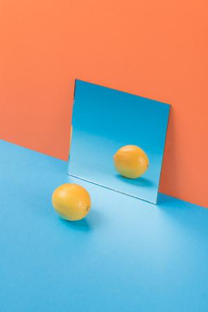 Image of lemon on blue table isolated over orange background