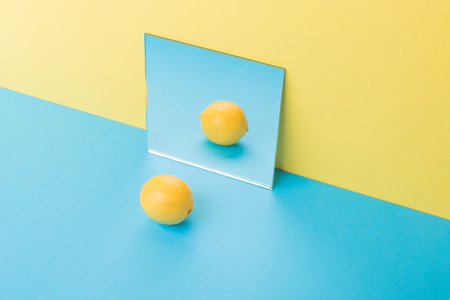 Image of lemon on blue table isolated over yellow background near mirror Stok Fotoğraf