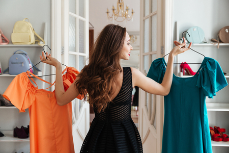 looking aside: Image of young lady standing in clothes shop indoors choosing dresses. Looking aside. Stock Photo