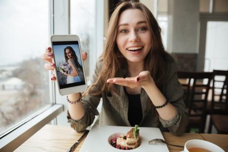 Glimlachende vrouw die foto toont die telefoon met behulp van terwijl het eten in koffie Stockfoto