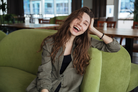Portrait of laughing young woman sitting in green armchair in cafe