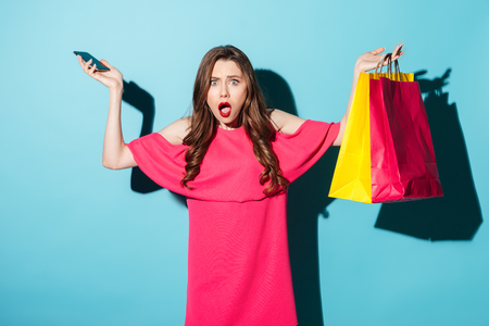 Image of a confused young brunette woman in pink dress holding mobile phone and shopping bags while looking at camera over blue background.