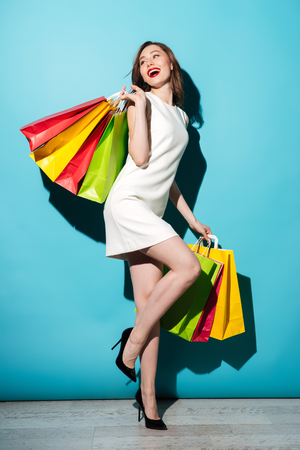 Full length portrait of a happy pretty girl holding colorful shopping bags and posing isolated over blue background