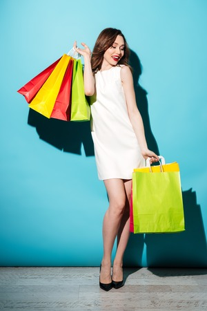 Full length portrait of an attractive cheerful woman holding colorful shopping bags and posing isolated over blue background Stock fotó