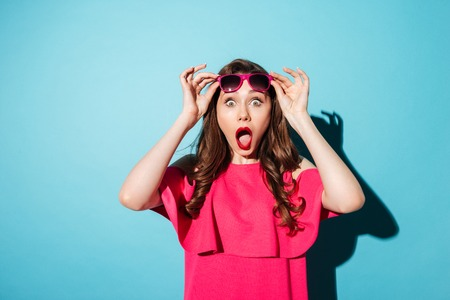 Portrait of a shocked young girl in dress looking at camera with her mouth open isolated over blue background