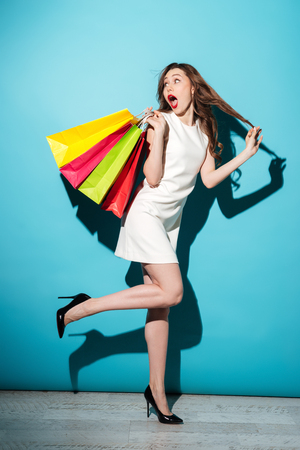 Full length portrait of a beautiful excited woman in dress running with colorful shopping bags isolated over blue background Stock Photo