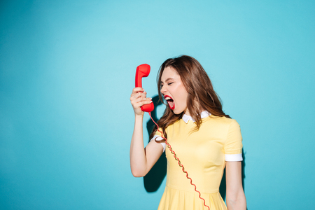 Portrait of an angry furious girl in dress screaming at retro telephone tube isolated over blue background Banco de Imagens