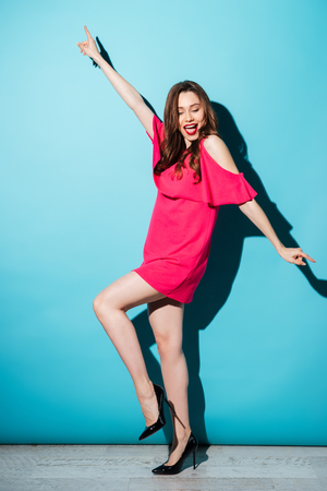 looking away from camera: Full length portrait of a smiling positive woman in dress dancing and having fun isolated over blue background Stock Photo