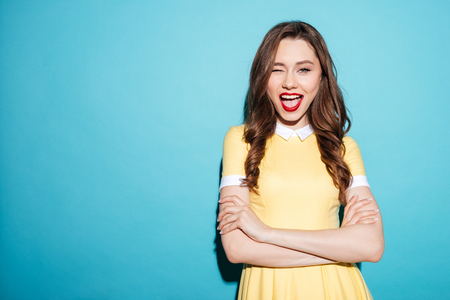 Portrait of cheerful pretty woman in dress standing and winking with her arms crossed isolated over blue background Stock Photo