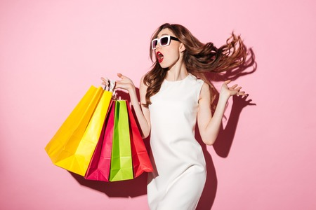 Photo of a pretty young brunette woman in white summer dress wearing sunglasses posing with shopping bags and looking aside over pink background.