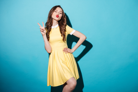 Portrait of an attractive playful girl in dress showing peace gesture and winking isolated over blue background Stock Photo