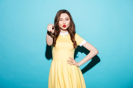 indicate: Portrait of a pretty flirty woman in dress winking and pointing finger at camera isolated over blue background Stock Photo
