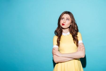 Retrato de uma linda garota decepcionada no vestido de pé com os braços dobrados e desviando o olhar isolado sobre fundo azul