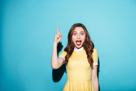 Portrait of a beautiful excited girl in dress pointing finger up at copyspace isolated over blue background Foto de archivo