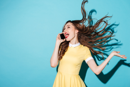 Portrait of a happy cheerful girl with long beautiful hair wearing dress and talking on mobile phone isolated over blue background