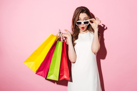 Image of a shocked young brunette lady in white summer dress wearing sunglasses posing with shopping bags and looking at camera over pink background. Archivio Fotografico