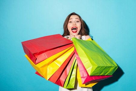 Portrait of a happy joyful girl holding colorful shopping bags and looking at camera isolated over blue background Stock Photo