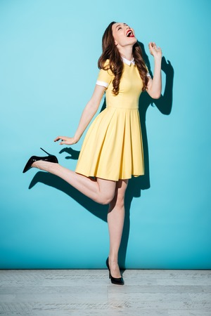Image of a happy young brunette woman in yellow dress posing and looking aside over blue background. 免版税图像