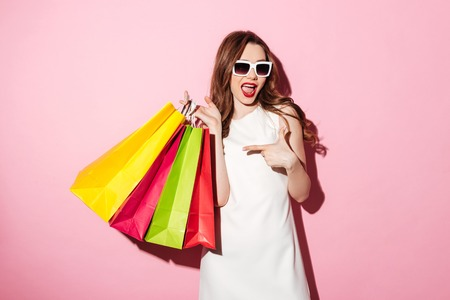 Image of an amazing young brunette woman in white summer dress wearing sunglasses posing with shopping bags and looking at camera over pink background while pointing.