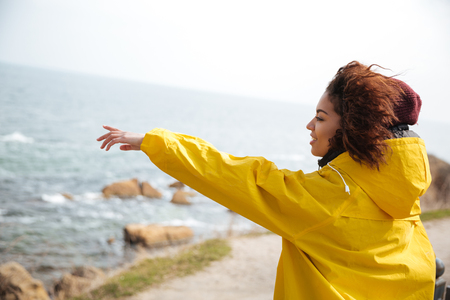 Young woman in cap and yellow coat smling and showing to the distance at sea Stock Photo