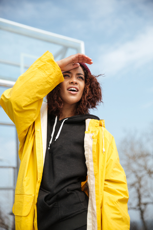 looking aside: Photo of concentrated african curly young lady wearing yellow coat walking outdoors. Looking aside. Stock Photo