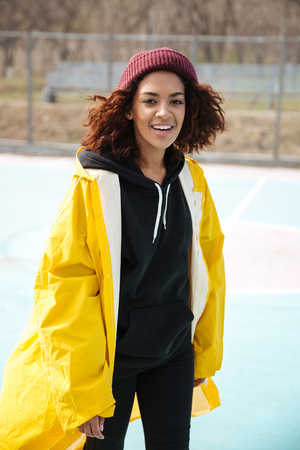 Photo of happy african young lady walking outdoors dressed in yellow raincoat. Looking at camera. 版權商用圖片