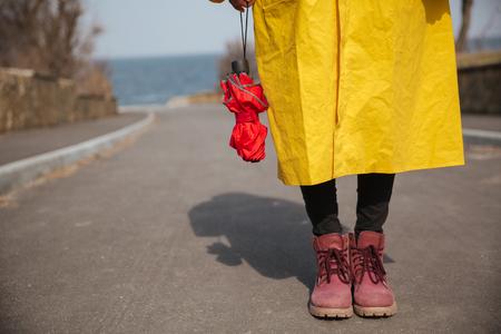 Cerrar la foto de las piernas de la mujer mientras ella sostiene rojo paraguas cerrado Foto de archivo - 80925178