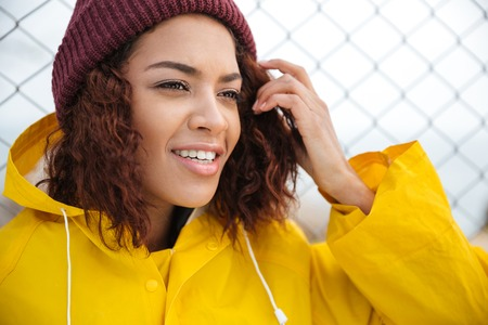 Picture of concentrated african young lady walking outdoors dressed in yellow raincoat. Looking aside.