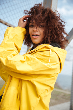 Image of happy african curly young lady wearing yellow coat walking outdoors. Looking at camera.