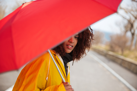 Smiling woman with red umbrella sitting near road