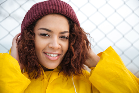 Image of smiling african young lady walking outdoors dressed in yellow raincoat. Looking at camera.