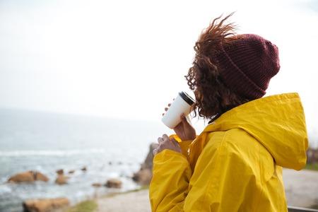 Woman in raincoat with coffee looking at sea on sunny day. Stok Fotoğraf