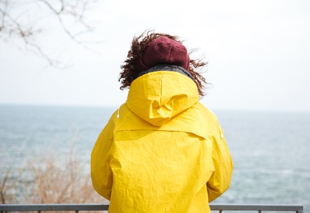 Backview shot of woman looking away at sea in yellow raincoat Stok Fotoğraf