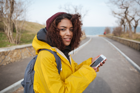 Woma with curly hair in yellow raincoat near road using smartphone