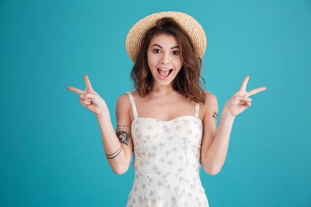 Happy excited girl in summer clothes showing peace gesture with two hands isolated over blue background Imagens - 80936578